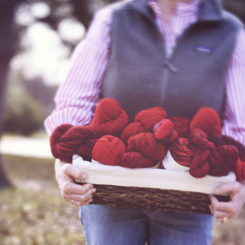 Holding a basket of red yarn