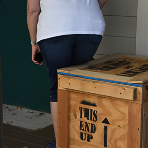 Woman about to sit on wooden crate